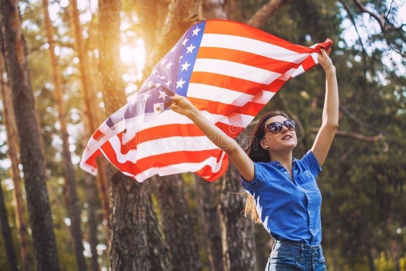Glückliche lächelnde junge Frau mit nationaler amerikanischer Flagge draußen lizenzfreie stockfotografie