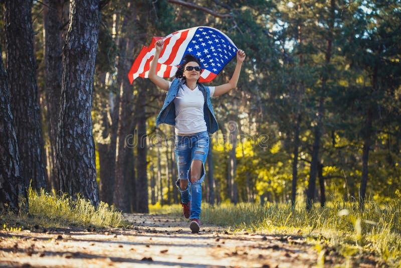 Glückliche lächelnde junge Frau mit nationaler amerikanischer Flagge draußen stockfotografie