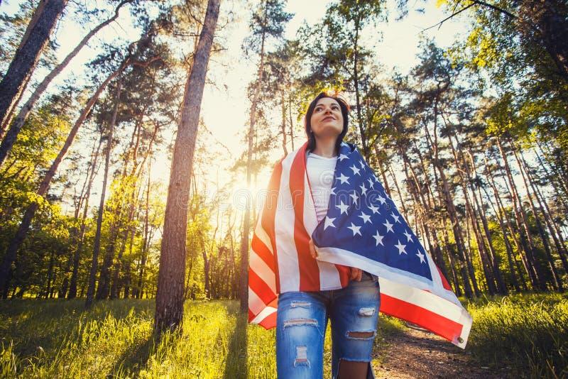 Glückliche lächelnde junge Frau mit nationaler amerikanischer Flagge draußen stockfotos