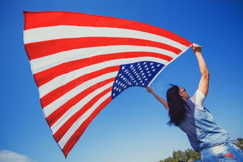 Glückliche lächelnde junge Frau mit nationaler amerikanischer Flagge gegen den blauen Himmel stockfoto