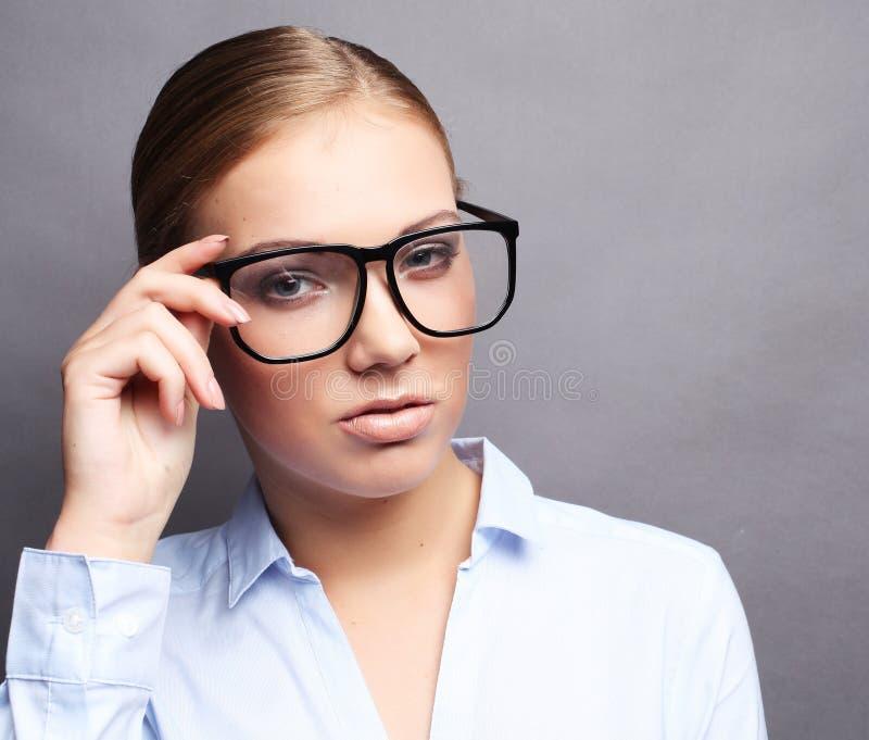 Glückliche lächelnde junge Geschäftsfrau in den Gläsern, über grauem backgr stockbilder