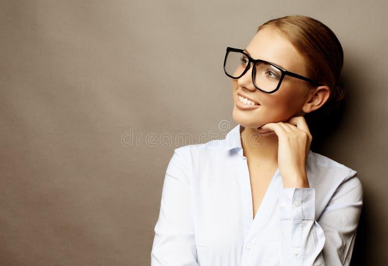 Glückliche lächelnde junge Geschäftsfrau in den Gläsern, über grauem backgr lizenzfreie stockbilder