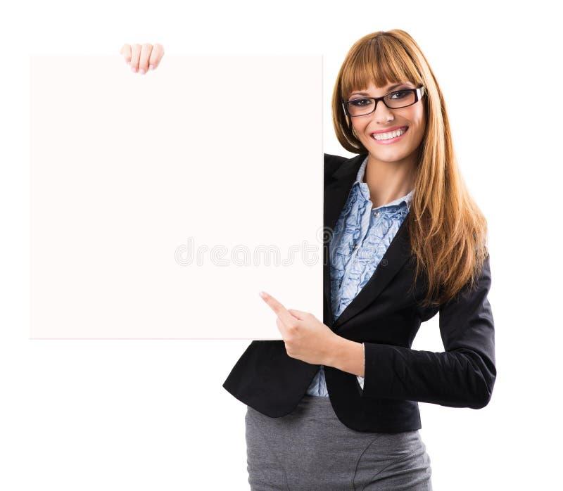 Glückliche lächelnde junge Geschäftsfrau, die leeres Schild zeigt lizenzfreie stockfotografie