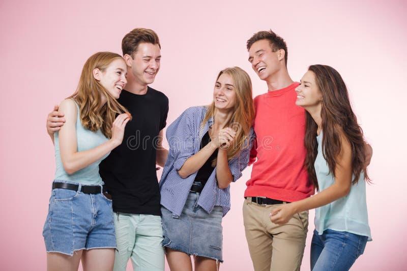Glückliche lächelnde junge Gruppe Freunde, die zusammen sprechend und lachend stehen Beste Freunde stockbild