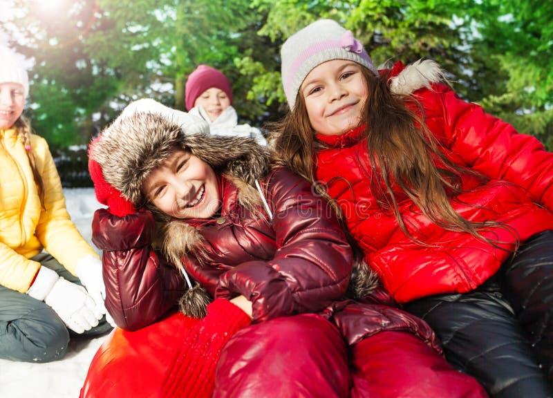 Glückliche lächelnde Mädchen, die auf dem roten Eisboot sitzen stockbild