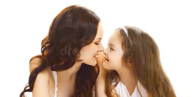 Glückliche lächelnde Mutter der Porträtnahaufnahme mit weniger Kindertochter, die einander lokalisiert auf Weiß betrachtet stockfoto