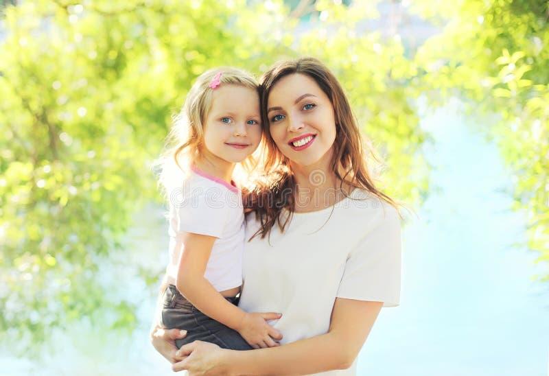 Glückliche lächelnde Mutter des Porträts, die Kindertochter im Sommer umarmt stockfotografie
