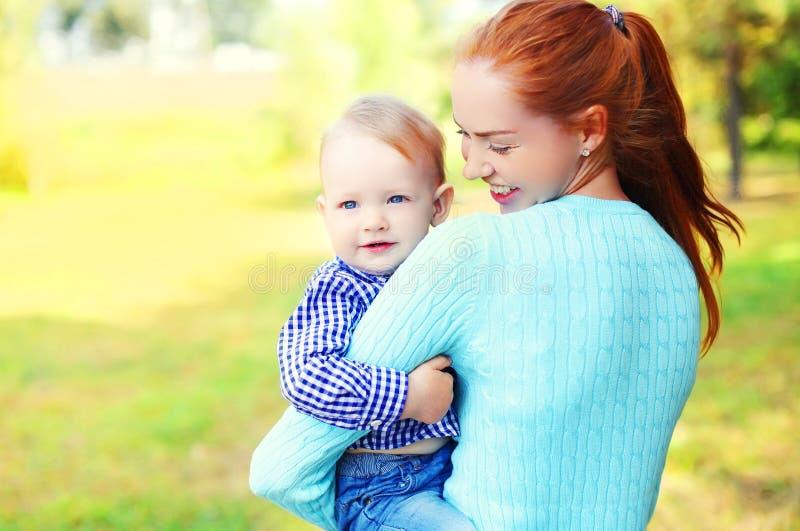 Glückliche lächelnde Mutter des Porträts und Sohnkind draußen lizenzfreie stockfotografie