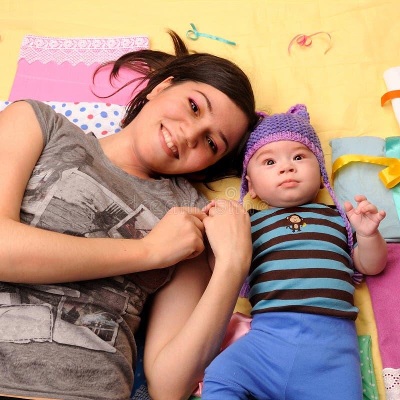 Glückliche lächelnde Mutter und Baby, die Kamera liegt und betrachtet stockbild