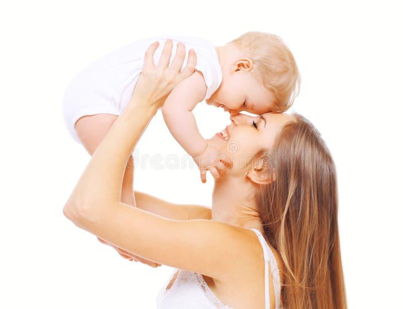 Glückliche lächelnde Mutter und Baby, die Spaß auf weißem Hintergrund hat lizenzfreie stockbilder
