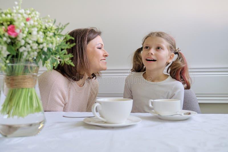 Glückliche lächelnde Mutter und kleine Tochter, die bei Tisch von den Schalen trinkt lizenzfreie stockfotos