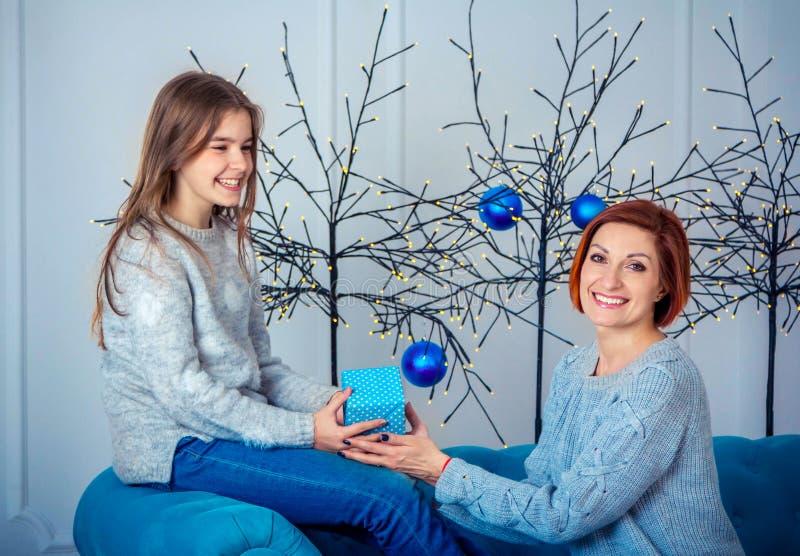 Glückliche lächelnde Mutter und Tochter, Holdinggeschenkbox, sitzend auf dem Sofa mit Weihnachtsdekorationen stockbild