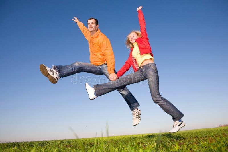 Glückliche lächelnde Paare, die in blauen Himmel springen lizenzfreies stockbild