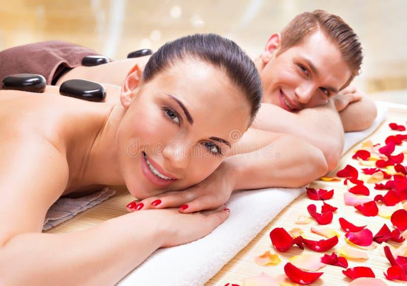 Glückliche lächelnde Paare, die im Badekurortsalon sich entspannen stockfotografie