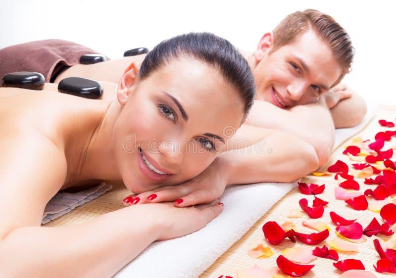 Glückliche lächelnde Paare, die im Badekurortsalon sich entspannen lizenzfreie stockfotos