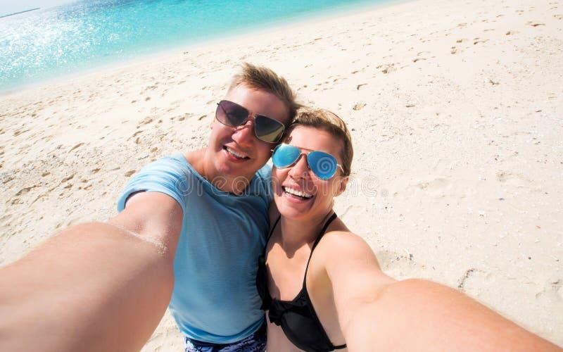Glückliche lächelnde Paare, die selfie auf einem Strand machen lizenzfreie stockfotografie