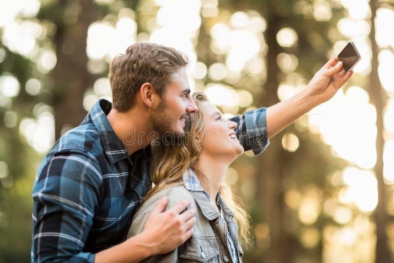 Glückliche lächelnde Paare, die selfies umfassen und nehmen stockfotografie
