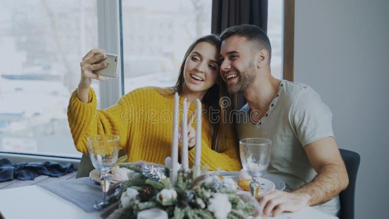 Glückliche lächelnde Paare, die zu Mittag essen und zuhause selfie Porträt mit Smartphone am Café nehmen stockbilder