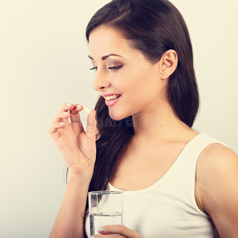 Glückliche lächelnde positive Frau, welche die Pille isst und das gla hält lizenzfreie stockfotografie