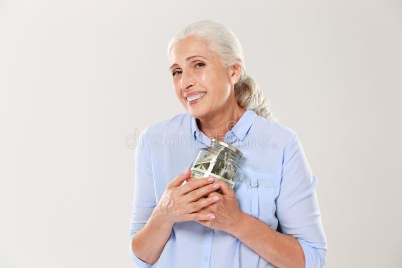 Glückliche lächelnde reife Frau, die ihr Glasgefäß mit Dollar umarmt stockfoto