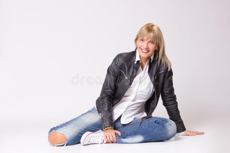 Glückliche lächelnde reife Frau 40s, die auf zufällige Kleidung des Bodens legt lizenzfreie stockbilder