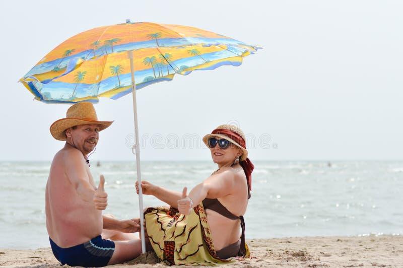 Glückliche lächelnde reife Paare, die draußen an der Küste auf sandigem Strand sitzen lizenzfreie stockbilder