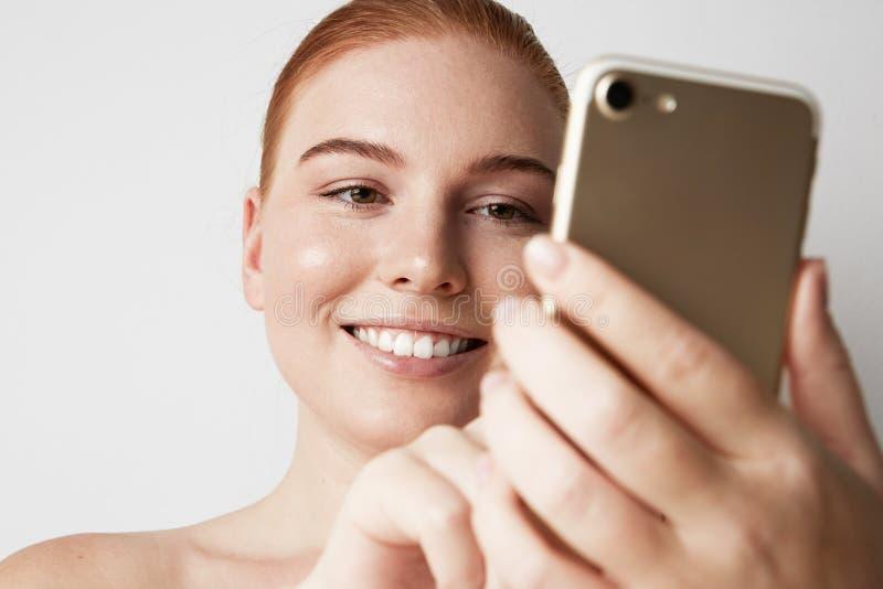 Glückliche lächelnde Rothaarigefrau, die Handy über grauem Hintergrund verwendet nahaufnahme lizenzfreies stockbild