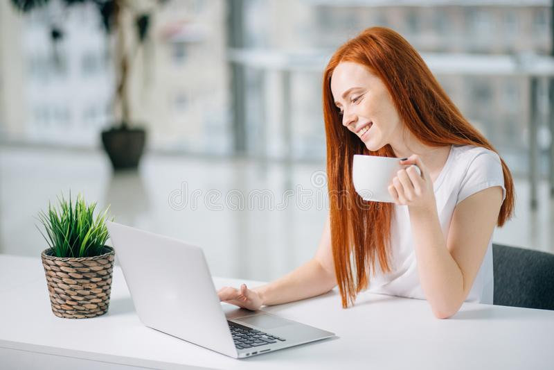 Glückliche lächelnde Rothaarigefrau, die mit Laptop und trinkendem Kaffee arbeitet lizenzfreies stockfoto