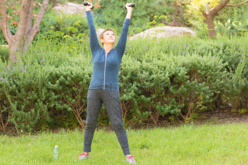 Glückliche lächelnde schöne ältere Frau, die Sportübungen mit Dummköpfen in einem Park an einem sonnigen Tag tut lizenzfreie stockfotos