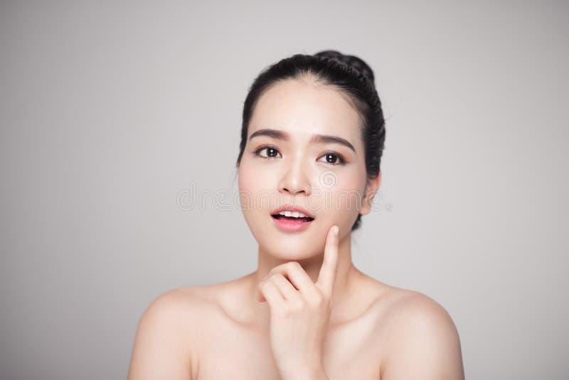 Glückliche lächelnde schöne asiatische Frau, die ihr Gesicht berührt lizenzfreie stockfotos