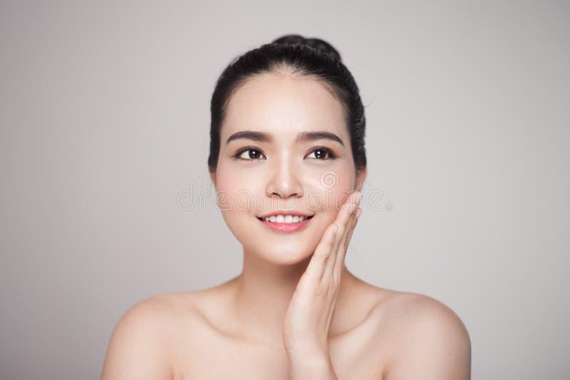 Glückliche lächelnde schöne asiatische Frau, die ihr Gesicht berührt lizenzfreies stockfoto