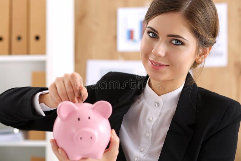 Glückliche lächelnde schöne Geschäftsfrau und piggybank lizenzfreie stockfotografie