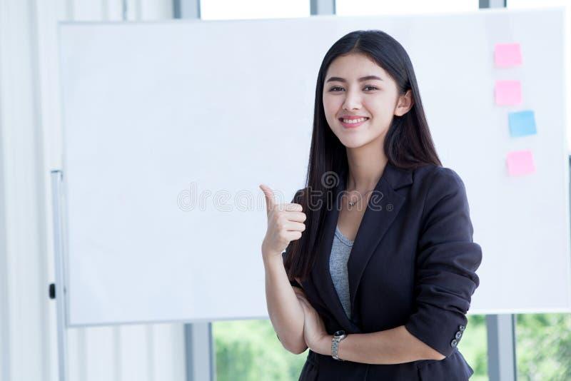 Glückliche lächelnde schöne junge asiatische Geschäftsfrau-Showdaumen oben lokalisiert auf Hintergrund des weißen Brettes im Büro lizenzfreies stockfoto