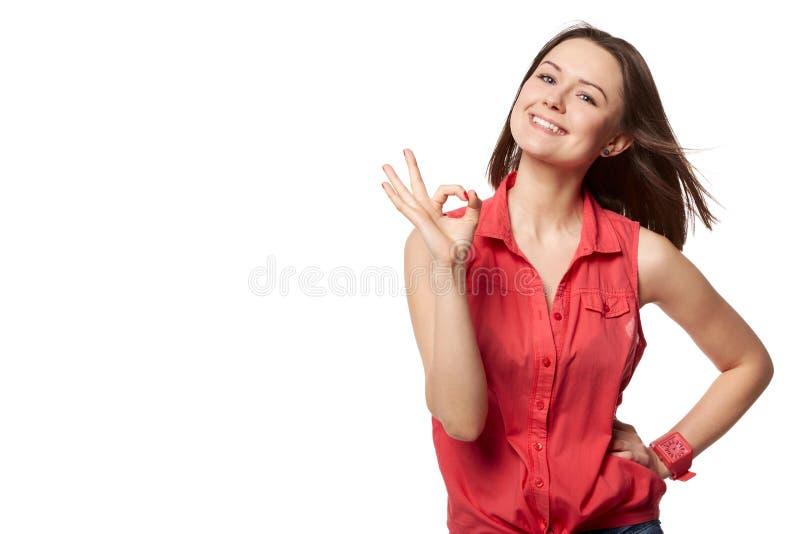 Glückliche lächelnde schöne junge Frau, welche die okaygeste, lokalisiert über Weiß zeigt stockfotografie