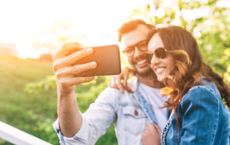 Glückliche lächelnde schöne Paare, die ein selfie Foto machen stockbild