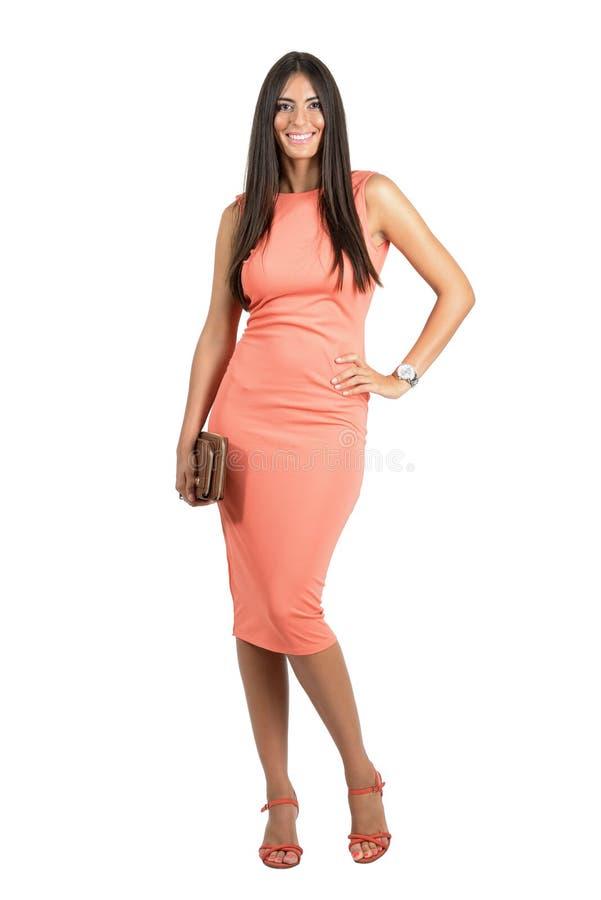 Glückliche lächelnde Schönheit im eleganten Abendkleid, welches die Tasche aufwirft an der Kamera hält lizenzfreie stockfotos