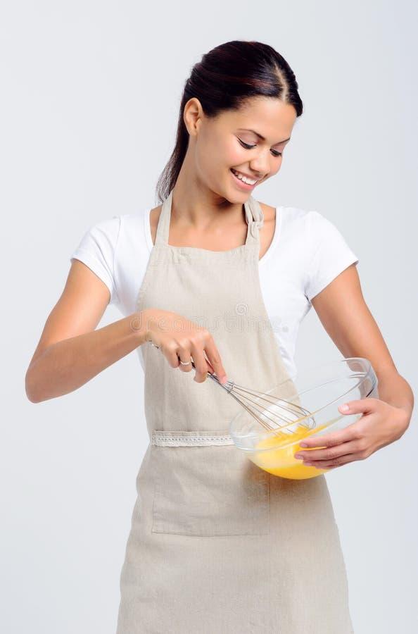 Glückliche lächelnde schlagende Eier der Frau stockbilder
