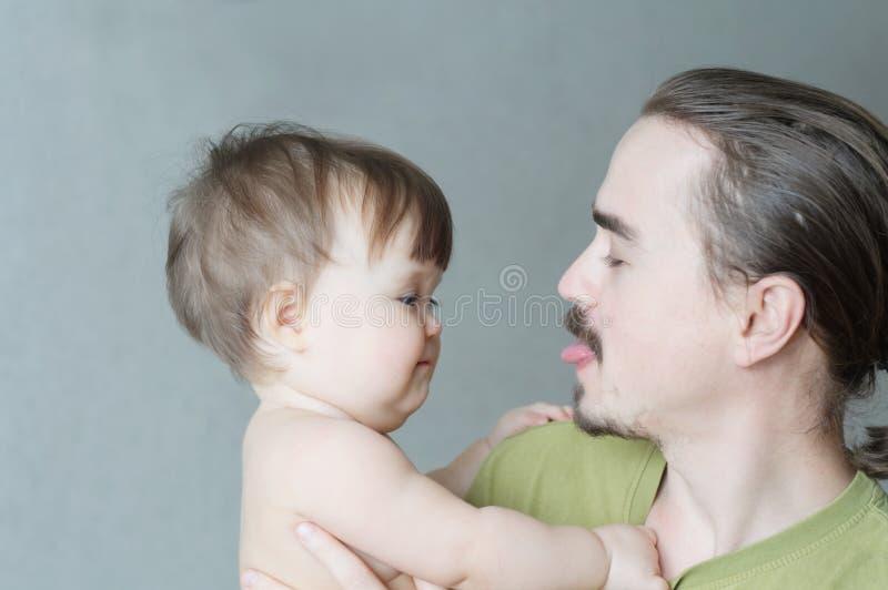 Glückliche lächelnde Vater- und Babytochter, die Porträt spielt Glück im einfachen Lebensstil bärtiger junger Mann, der Zunge zei lizenzfreies stockfoto