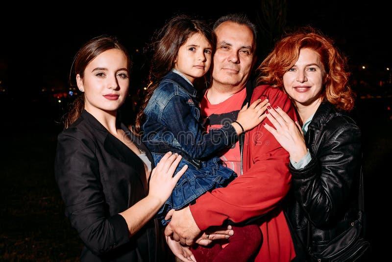 Glückliche lächelnde vierköpfige Familie, die in camera nachts aufwirft stockbilder