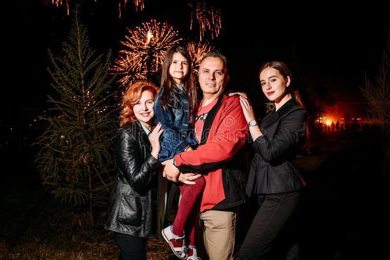 Glückliche lächelnde vierköpfige Familie nachts auf dem Hintergrund von Feuerwerken lizenzfreies stockbild
