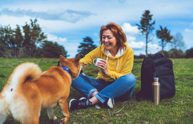 Glückliche Lächelnmädchenholding im Hand-Schalengetränk, das mit rotem japanischem Hund-shiba inu auf grünem Gras im Freiennaturp lizenzfreie stockbilder