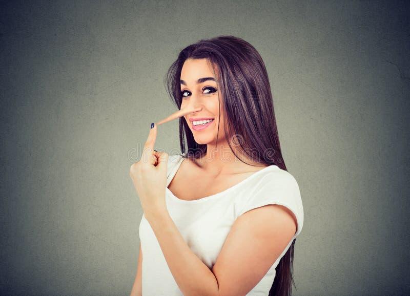 Glückliche Lügnerfrau mit langer Nase stockfoto