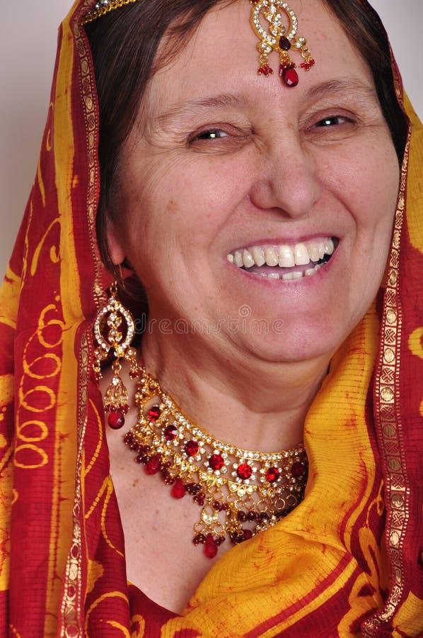Glückliche lachende ältere Frau in der traditionellen indischen Kleidung und in den jeweleries lizenzfreies stockfoto