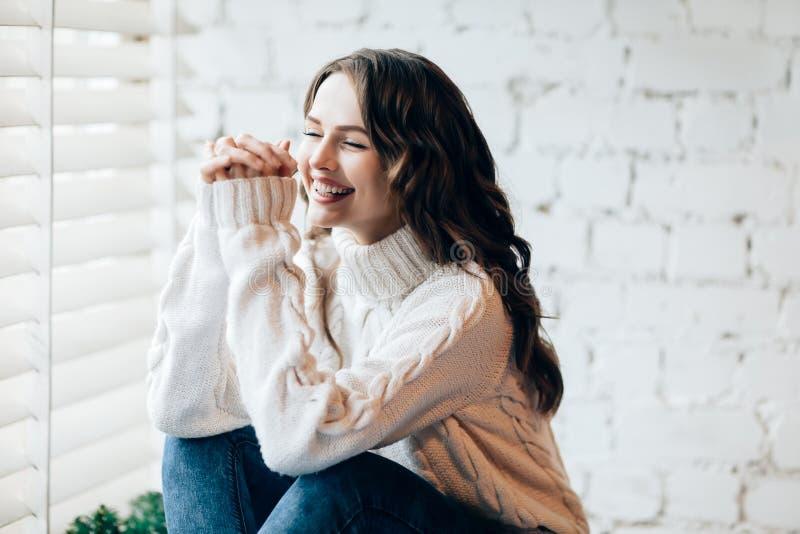 Glückliche lachende Frau, die auf Fensterbrett sich entspannt lizenzfreie stockbilder