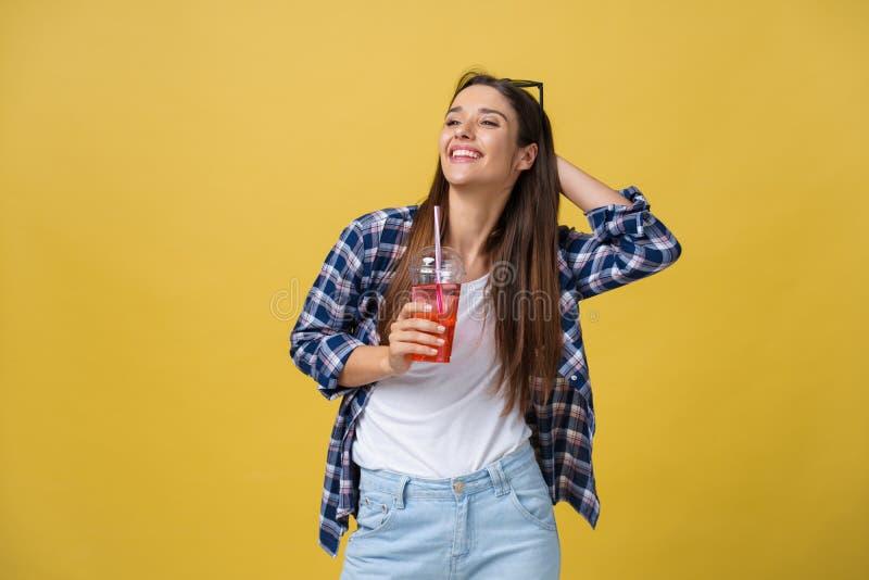 Glückliche lachende Frau, die einen zufälligen Stoff trinkt ein tropisches Cocktail, lokalisiert auf gelbem Hintergrund trägt lizenzfreie stockfotografie