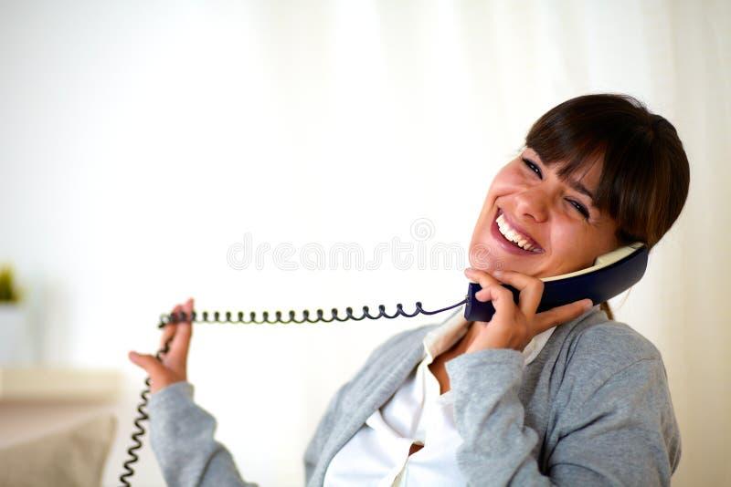 Glückliche lachende Frau, die sich zu Hause am Telefon unterhält stockfotografie