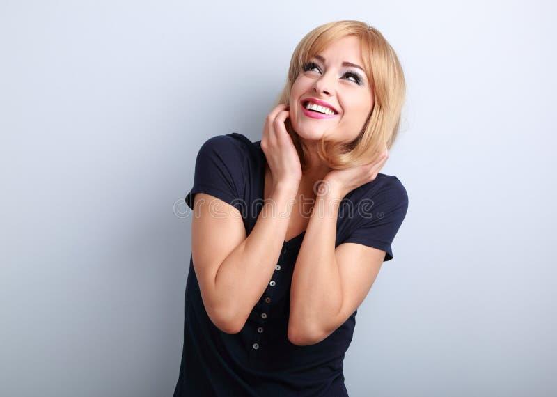 Glückliche lachende junge Frau mit der blonden Frisur, die oben auf b schaut lizenzfreies stockbild