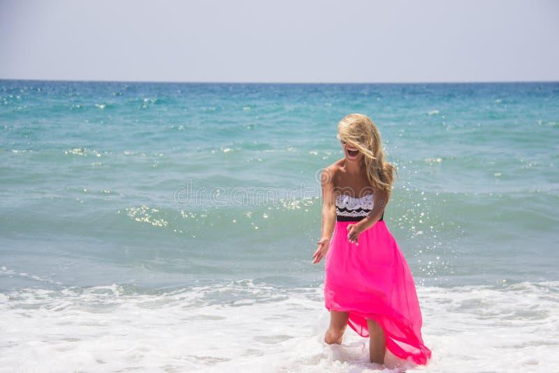 Glückliche lachende junge kaukasische Frau, die Tag am Strand auf Sommerferien genießt Gemischtrassiges Mädchen der gesunden lebe lizenzfreie stockbilder