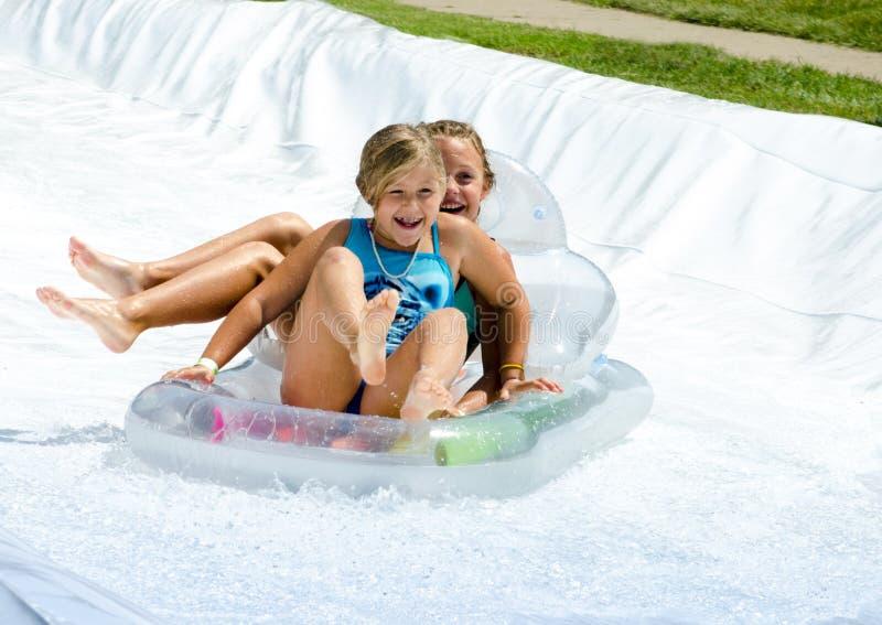 Glückliche lachende Mädchen auf Wasserrutschen stockfotografie