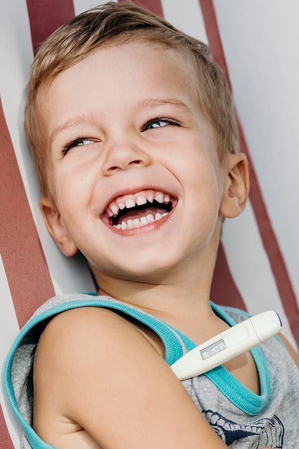 Glückliche lachende messende Temperatur des kleinen Jungen stockfotos